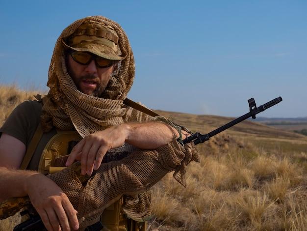 Foto de close de um atirador mercenário com roupas camufladas sob o sol escaldante