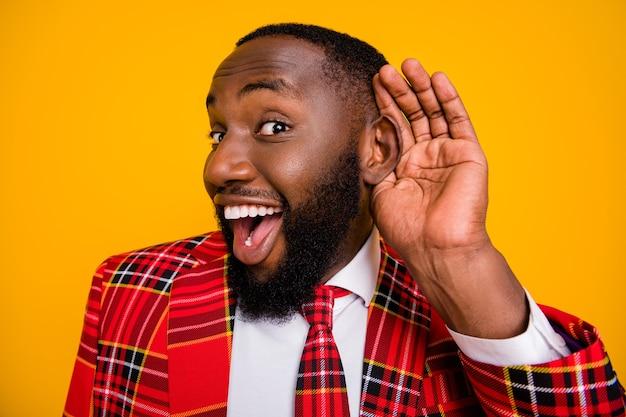 Foto de close de um cara engraçado astuto segurando o braço perto do ouvido para ouvir