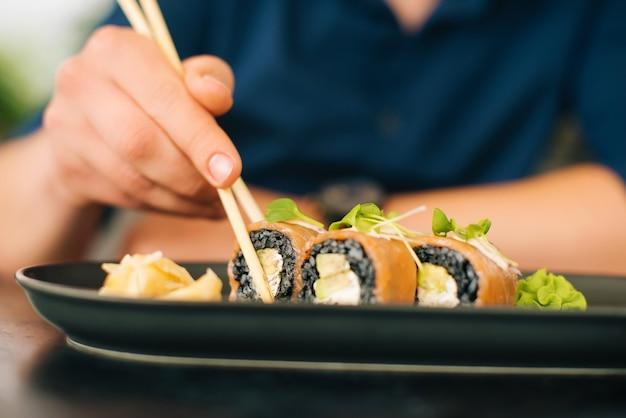 Foto de close de um homem comendo rolinho chinês com arroz preto