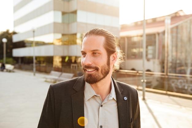 Foto de close de um homem corporativo ou gerente de escritório de terno sorrindo, em frente ao centro de negócios no centro da cidade