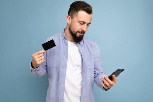Foto de close de um jovem moreno bonito e sorridente com a barba por fazer, vestindo uma camisa azul casual