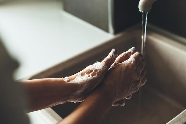Foto de close de um procedimento de lavagem das mãos com sabão durante uma situação de pandemia