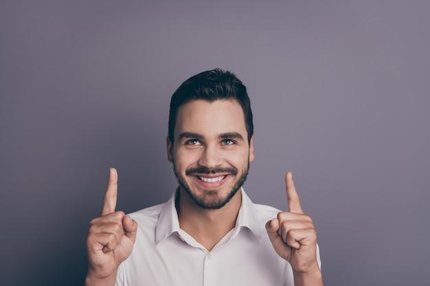Foto de close de um vendedor bonito indicando o espaço vazio com os dedos
