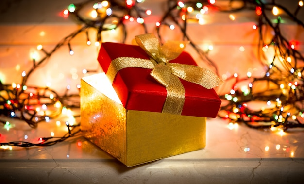 Foto de close de uma caixa de presente aberta com luz saindo dela