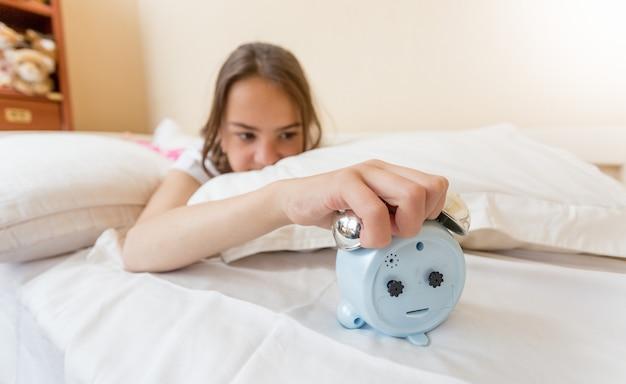 Foto de close de uma garota irritada pegando o despertador