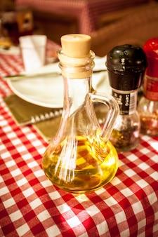 Foto de close de uma garrafa de vidro de azeite de oliva na mesa do restaurante