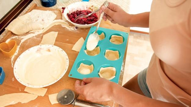 Foto de close de uma jovem dona de casa servindo creme ou creme nos saborosos cupcakes em formas de silicone