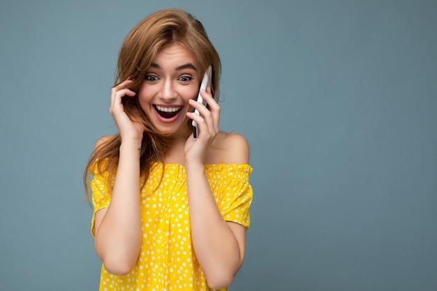 Foto de close de uma jovem loira espantada de forma positiva usando um elegante vestido amarelo de verão