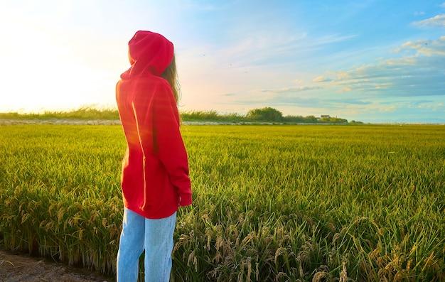 Foto de close de uma jovem vestida de vermelho, alegremente em pé em um campo verde em um dia ensolarado