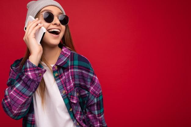Foto de close de uma linda jovem loira positiva e feliz vestindo uma camisa roxa hipster