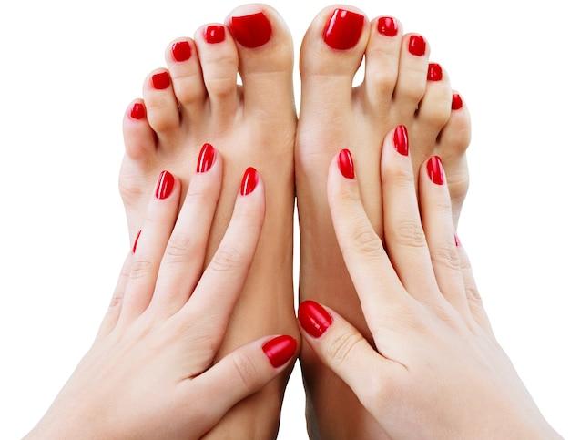 Foto de close de uma linda mulher com pés com pedicure e mãos com manicure