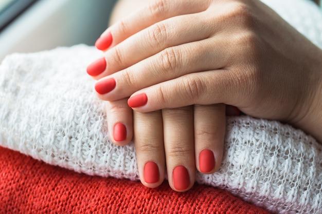Foto de close de uma linda mulher com unhas vermelhas