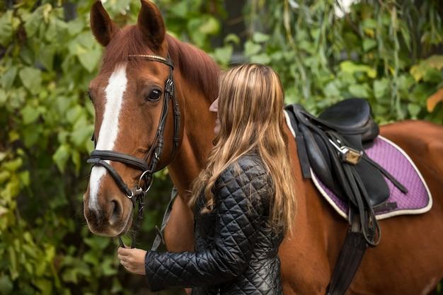 Foto de close de uma linda mulher segurando um cavalo pelas rédeas