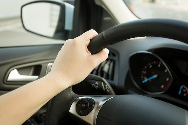 Foto de close de uma mão feminina segurando o volante com botões