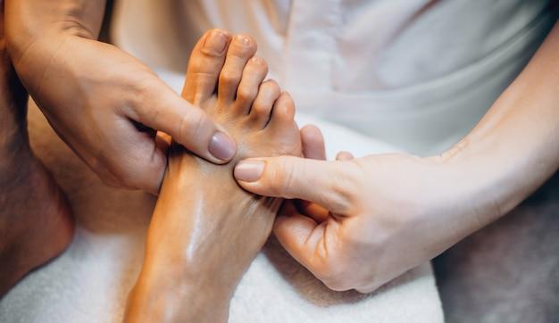Foto de close de uma massagista caucasiana fazendo uma sessão de massagem nos pés com uma cliente do spa