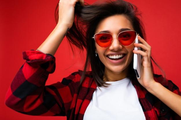 Foto de close de uma morena jovem sorridente e atraente, usando uma camiseta branca elegante e óculos de sol vermelhos