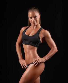 Foto de close de uma mulher de esportes vestindo roupas esportivas pretas no escuro