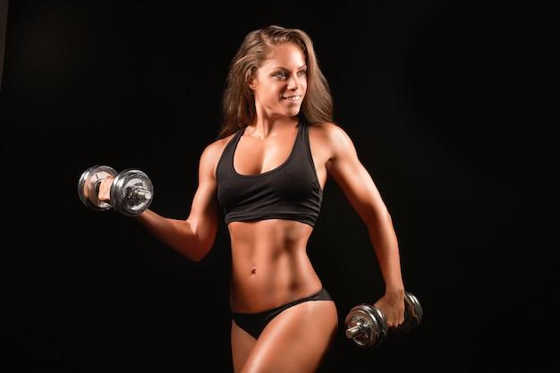 Foto de close de uma mulher de esportes vestindo roupas esportivas pretas sobre o escuro levantando halteres