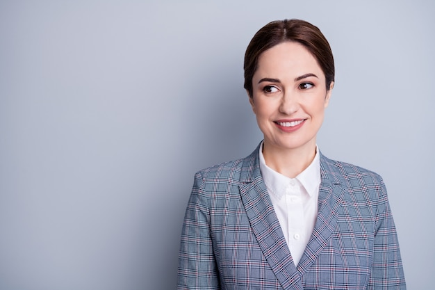 Foto de close de uma mulher de negócios atraente com um sorriso radiante bom humor professor qualificado profissão ocupação olhar lado interessado usar blazer xadrez camisa branca isolada cor de fundo cinza
