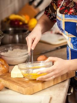 Foto de close de uma mulher misturando ovos em uma tigela de vidro