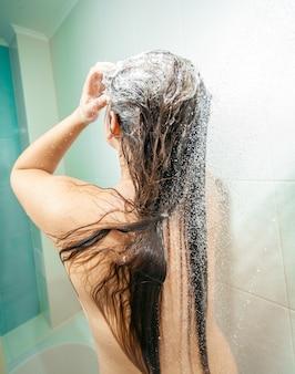 Foto de close de uma mulher morena sexy ensaboando a cabeça no chuveiro