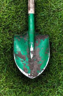 Foto de close de uma pá verde com solo na grama