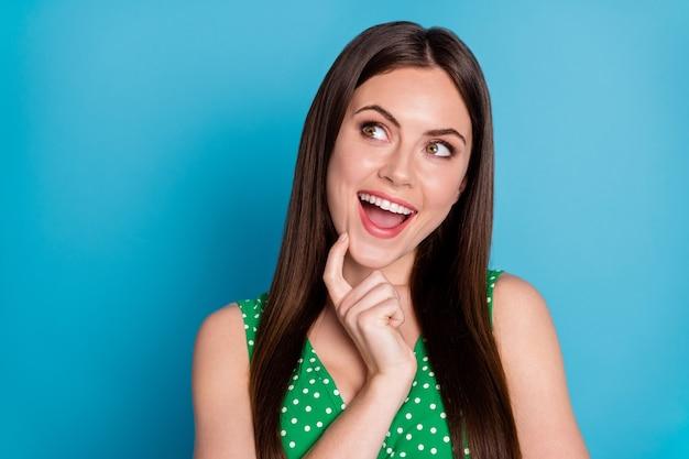 Foto de close de uma senhora bonita e atraente segurando o braço no queixo inteligente criativo inteligente interessado olhar para cima o espaço vazio usar camiseta regata pontilhada verde isolado fundo de cor azul
