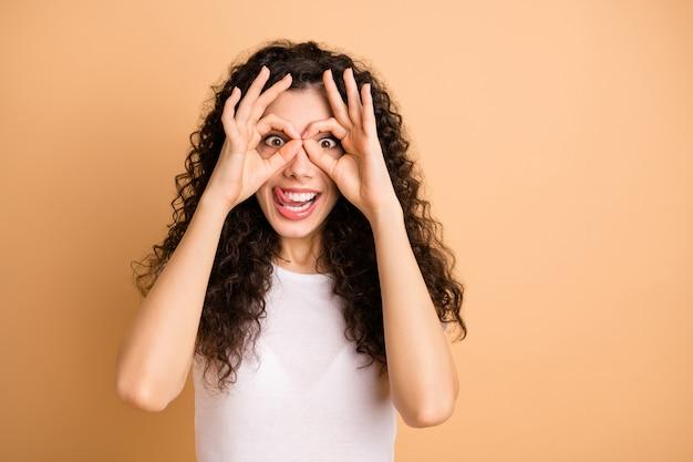 Foto de close de uma senhora engraçada, com um humor brincalhão, segurando os dedos redondos em formato de especificações perto dos olhos, enfiando a língua, usar roupa casual branca isolada fundo bege