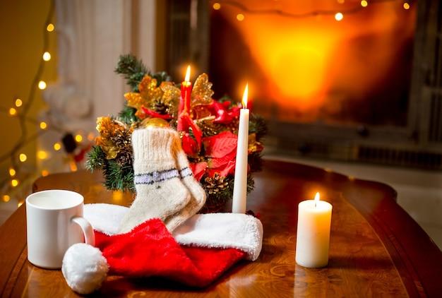 Foto de close de velas acesas, meias de lã e chapéu de papai noel deitado na mesa contra a lareira