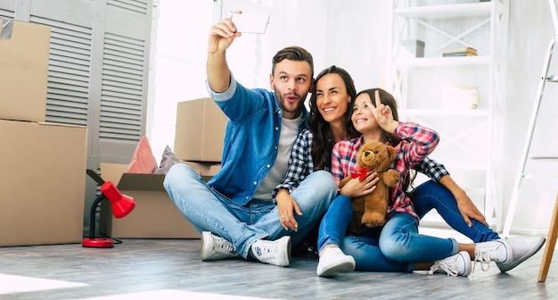 Foto de close, família alegre tirando selfie junta em sua nova casa em frente a uma pilha de caixas de papelão