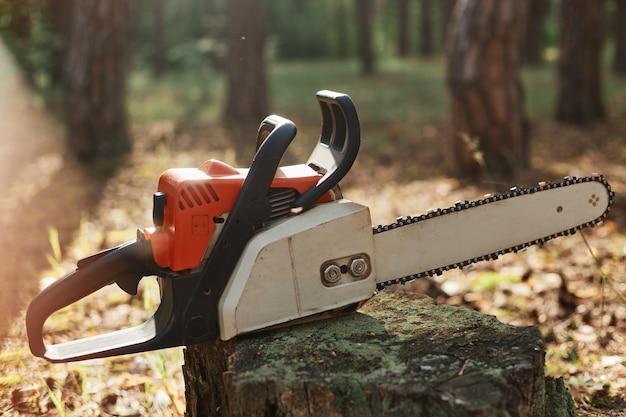 Foto de close-up ao ar livre de motosserra no toco de madeira