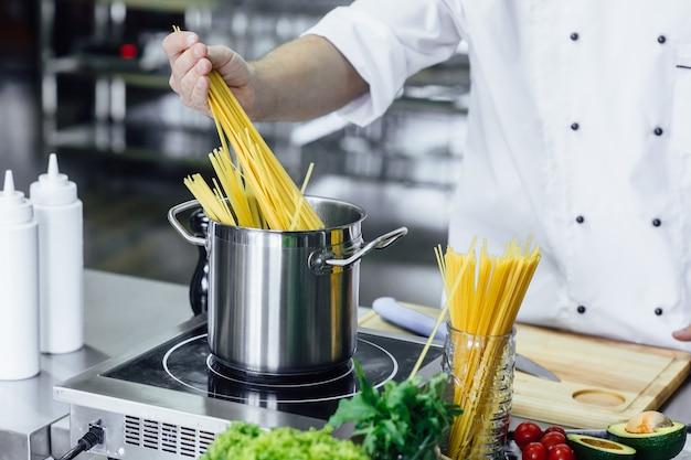 Foto de close up, cozinheiro chefe profissional, spahhetti fervente, equipamento de cozinha