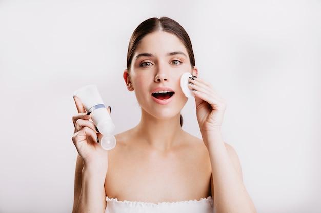 Foto de close-up da garota de olhos verdes, fazendo procedimento de spa na parede branca. mulher umedece o rosto com creme dove.