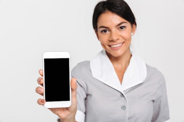 Foto de close-up da jovem mulher atraente de uniforme mostrando a tela do celular em branco, foco seletivo em exposição