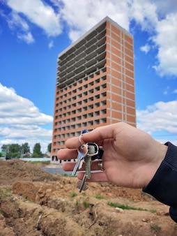 Foto de close-up da mão de um homem segurando as chaves de uma casa nova no fundo de um edifício residencial moderno
