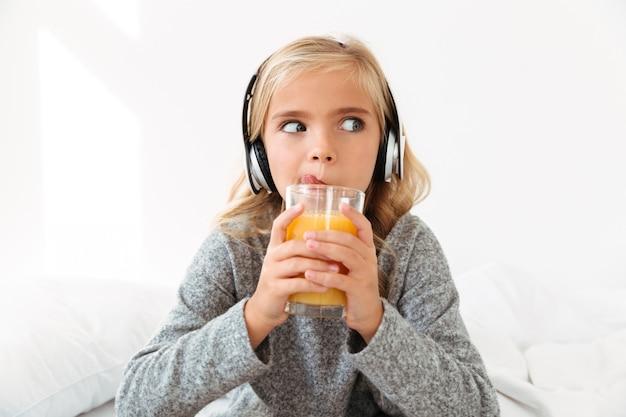 Foto de close-up da menina bonita em fones de ouvido lambendo enquanto bebe suco de laranja, olhando de lado