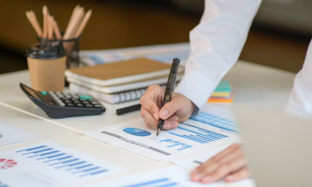 Foto de close-up da menina com uma caneta apontando para o gráfico para analisar dados.