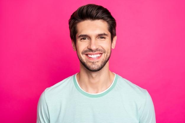 Foto de close-up da morena incrível machão revelando dentes brancos perfeitos e vestindo uma camiseta casual isolado fundo de cor rosa vibrante