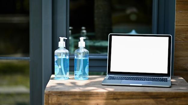 Foto de close-up da tela em branco do laptop de maquete com álcool gel em uma mesa de madeira.