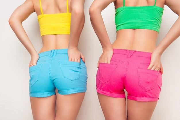 Foto de close-up das costas de uma mulher sexy em shorts coloridos, mãos nos bolsos