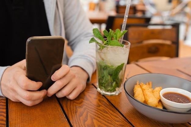 Foto de close-up das mãos de um homem na mesa de centro usando o smartphone ao lado do refrigerante mojito cocktai