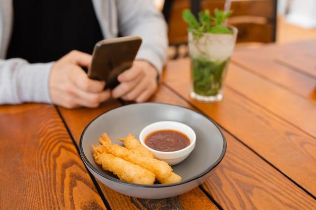 Foto de close-up das mãos do homem na mesa de centro com comer e beber, usando o smartphone