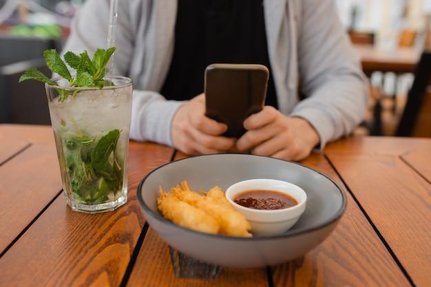 Foto de close-up das mãos do homem na mesa de centro usando smartphone, conceito de dispositivo móvel