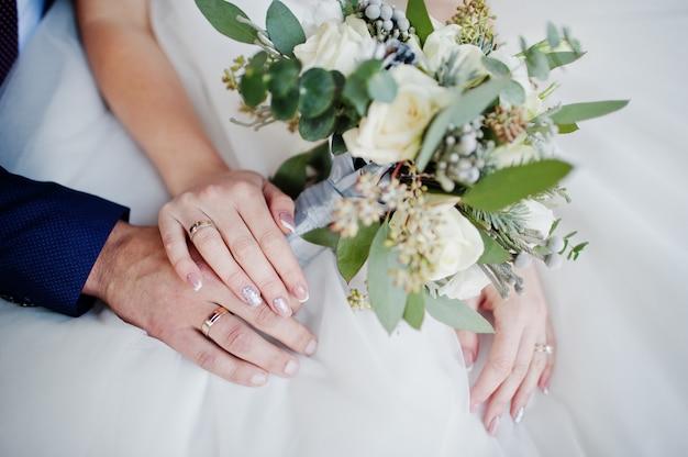 Foto de close-up das mãos do noivo e da noiva com anéis e buquê.