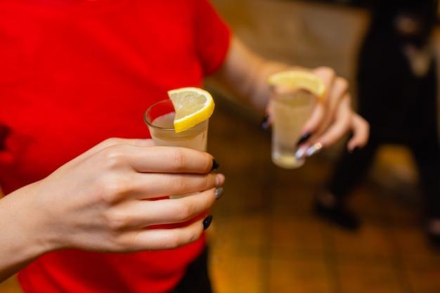 Foto de close-up de amigas brindando com copos de coquetéis durante uma festa no bar.