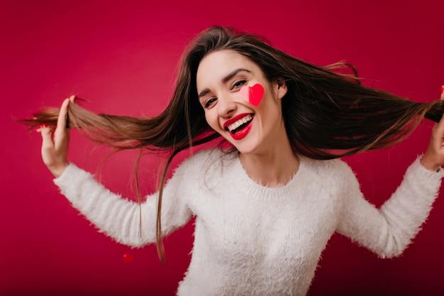 Foto de close-up de atraente garota caucasiana brincando com seus longos cabelos