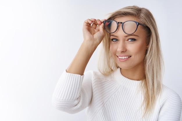Foto de close-up de atraente jovem e feliz mulher europeia no suéter tirando os óculos, parecendo encantado com o sorriso puro e otimista, promovendo uma sensação de bem-estar nos óculos em novos quadros sobre a parede branca.