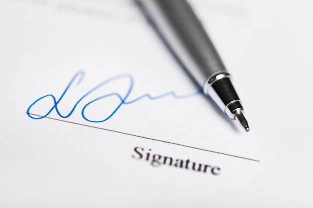 Foto de close-up de caneta de metal e assinatura