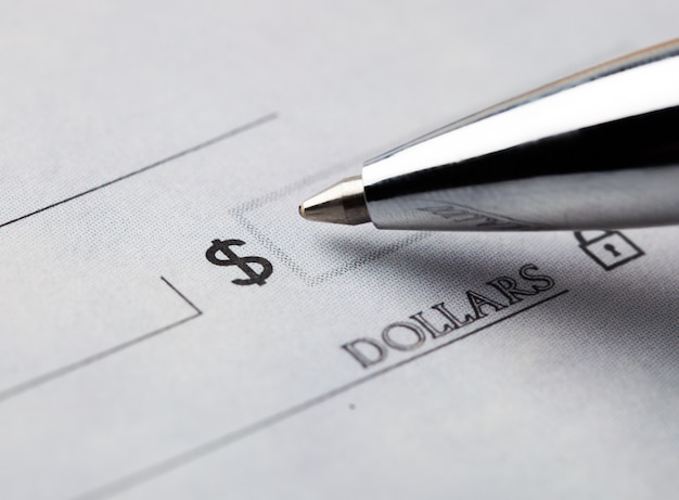 Foto de close-up de caneta de metal e dólar cantando