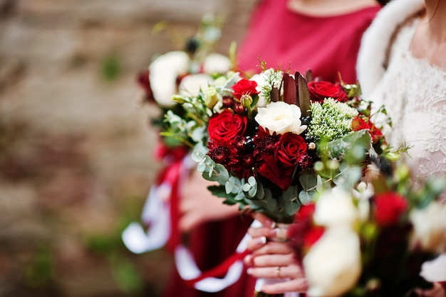 Foto de close-up de damas de honra e noiva segurando buquês nas mãos.